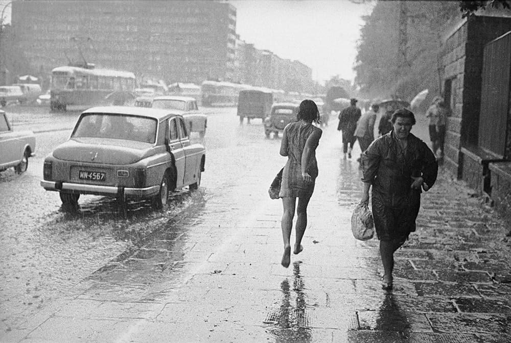 stara fotografia Kobieta biegnąca w deszczu, ul. Puławska w Warszawie, źródło: NAC