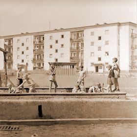 Dzieci bawiące się w piaskownicy na blokowisku. Nowa huta