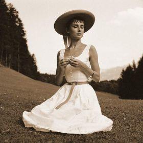 Audrey Hepburn na łące w kapeluszu - zdjęcie vintage